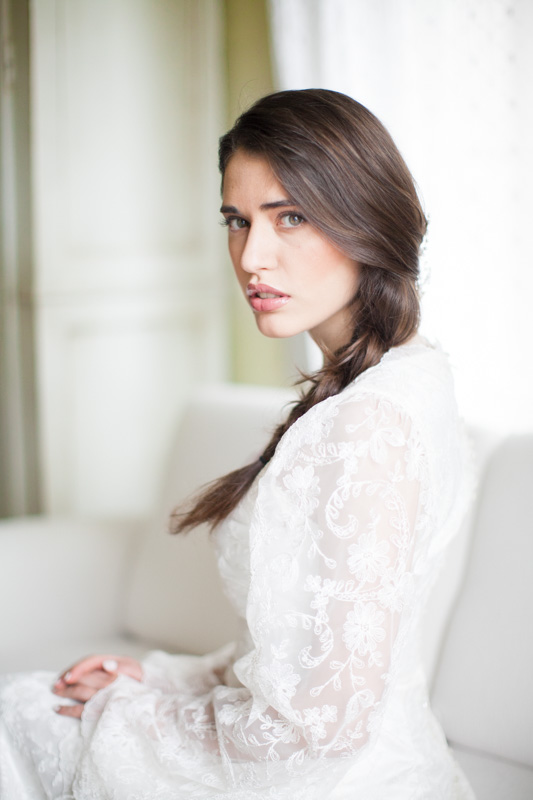 editorial style wedding portrait of an italian bride with a braid on a white couch in a rustic hotel room at urbino resort in italy