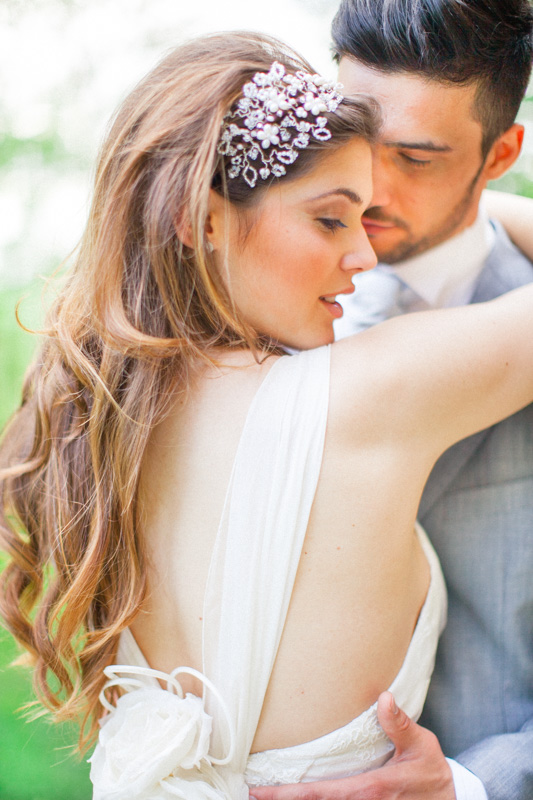 an italian bride and groom wedding portrait where you can see the back of the dress of the beautiful italian bride and a romantic groom looking at his wife