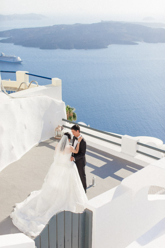 first look between a chinese bride and groom taken from above where you can see the blue sea and caldera view on the background at the sun rocks hotel in santorini