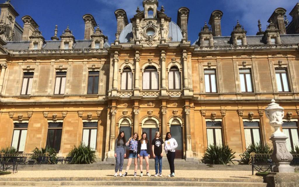 Teenage girls standing on stine steps outside Waddesdon Manor, a large country house.
