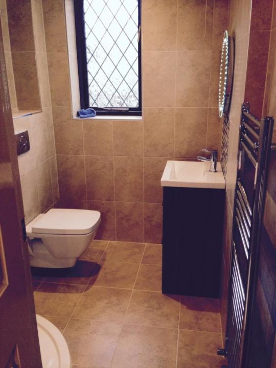 A pure white bathroom with oval bath, square double washbasin, large wall  mirror and