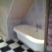 Free standing bath in asmall bathroom under the staircase.
