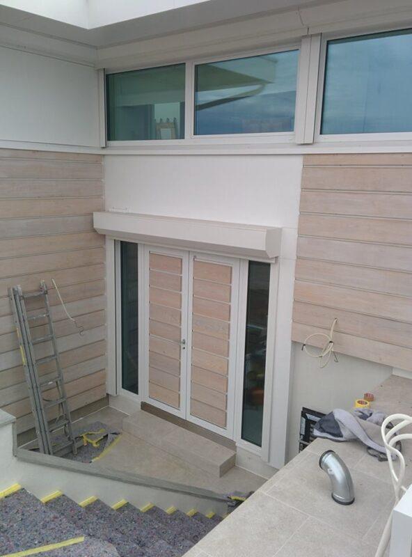 Inngangspartiet består av aluminiumsdører kledd i trepanel og to sidefelt