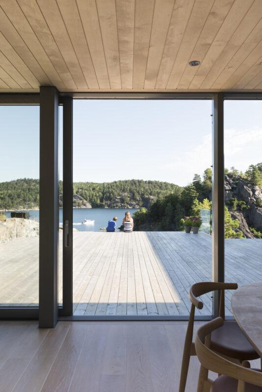 Hytten ble plassert rundt uteområdet og mot fjorden. Med mye glass og skyvedøren ASS 70.HI har familien god kontakt med omgivelsene