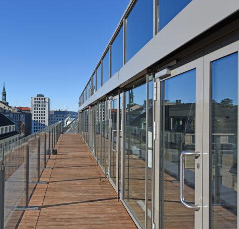 De tre øverste etasjene er terrassert slik at tilbygget virker mindre dominerende fra gateplan.