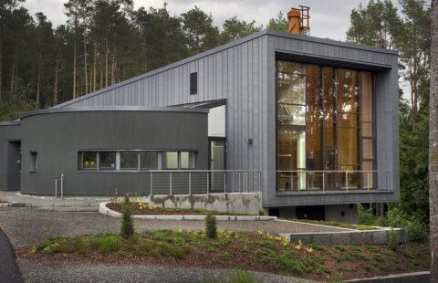 Mørkegrå aluminiumsprofiler står godt mot den grå båndtekkingen på fasaden