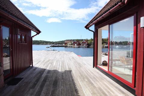 Fargen på skyvedøren harmonerer med fargen på fasadene på sjøbua og er en brunrød farge RAL 3011