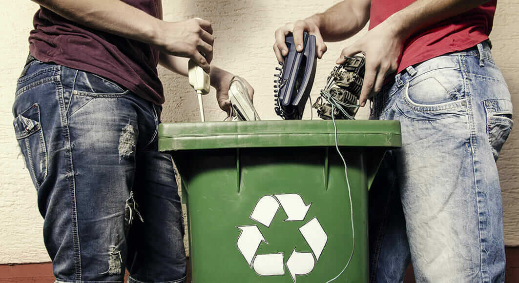 A photo of electrical items being placed into a recycling bin