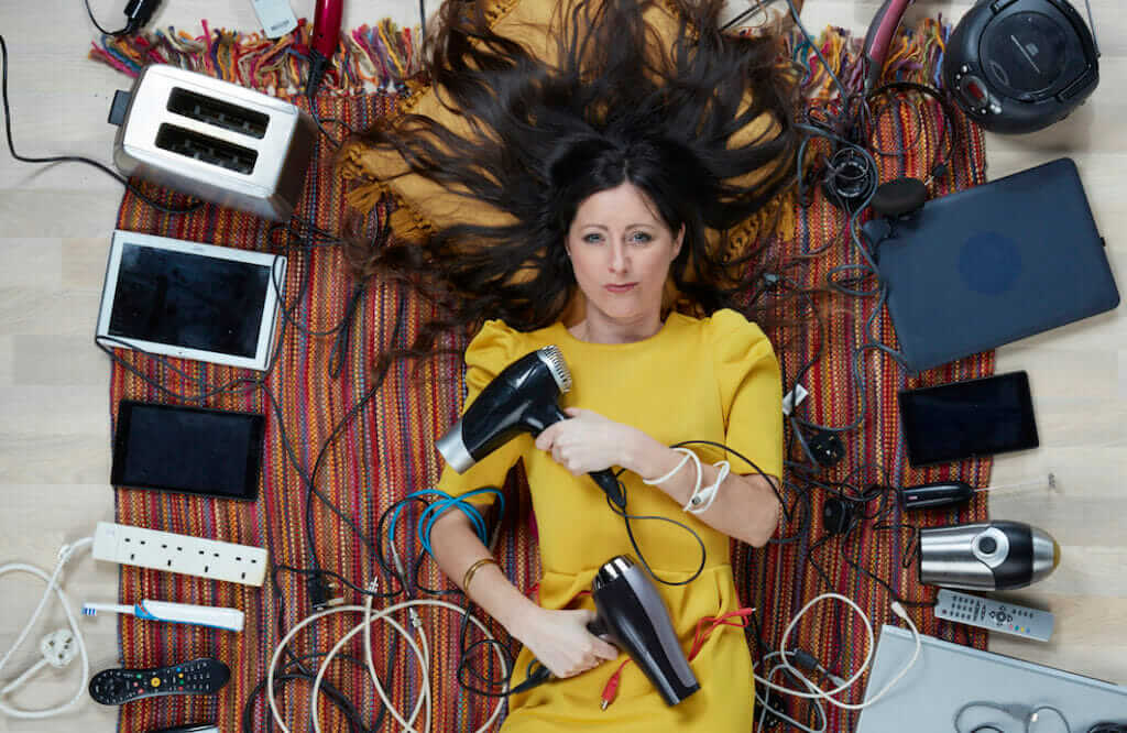 Photo of Natalie Fee, lying among electricals, by Gregg Segal