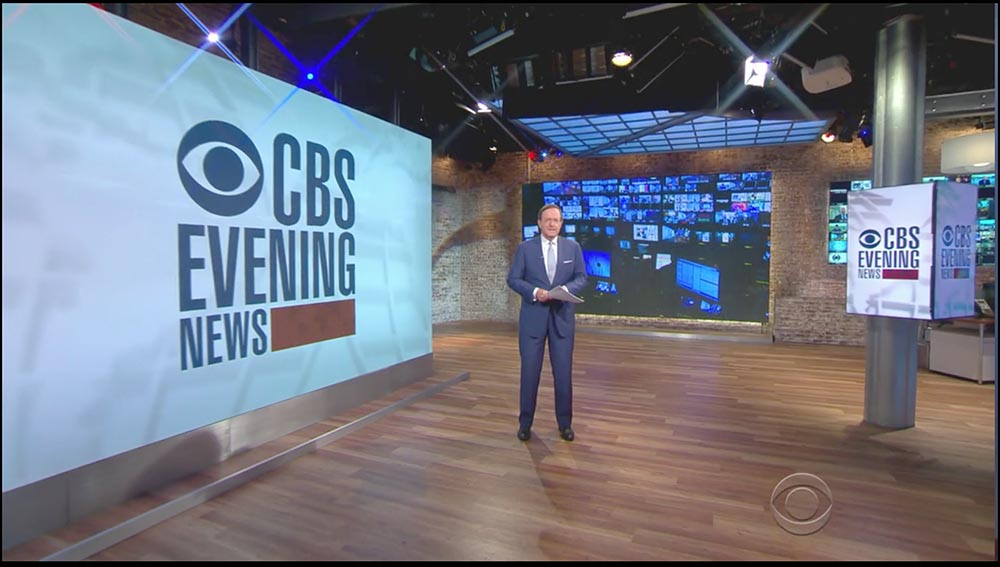 Figure 8.11 On the set of the CBS Evening News, anchor Anthony Mason is dwarfed by enormous video displays, one of which purports to show a newsroom.