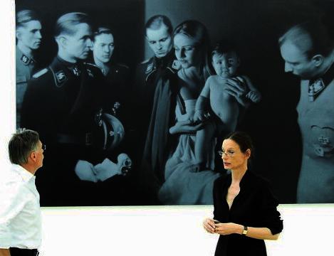 """Valerie Waibel mit Peter Klein vor dem großformatigen Bild """"Epiphany I"""" von Gottfried Helnwein."""