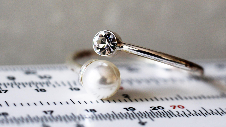 Maßband und Goldring mit Diamant und Perle