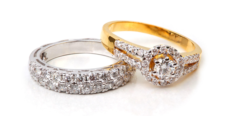 Goldring und Silberring mit Diamanten auf weißem Hintergrund