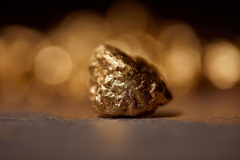 Stein aus Gold vor gold-schwarzem Hintergrund