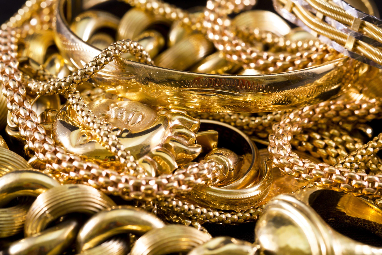 Goldene Schmuckstücke wie Ketten und Armreifen auf schwarzem Hintergrund