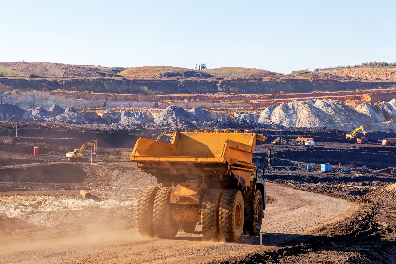 Ein Laster fährt in einer Bergbaugrube und fördert Gold