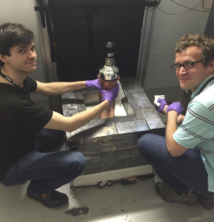 """Bjorn Scholz (gauche) et Grayson Ridge (droit) installent le plus petit des détecteurs de neutrinos dans la """"ruelle"""" des neutrinos au Spallation Neutron Source - Crédit : Juan Collar/University of Chicago"""