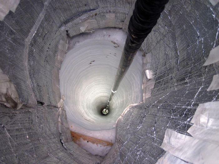 Un cable avec des chaines de détecteurs de neutrinos qui s'enfonce dans la glace pendant la construction du laboratoire IceCube au Pôle Sud - Crédit : NSF/B.Gudbjartsson