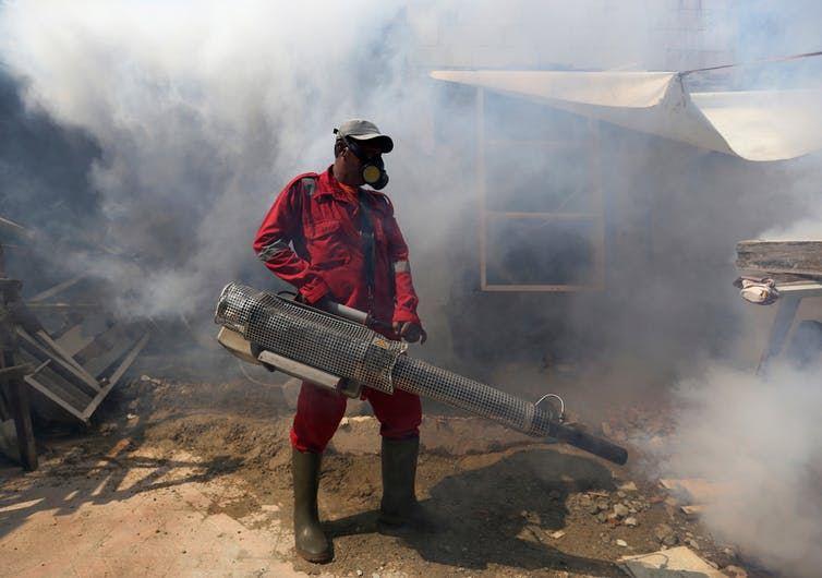 Un employé pulvérise de la brume anti-moustique pour tenter de contrôler la dengue dans un quartier de Jakarta, en Indonésie. Les zones à forte densité de population du pays sont souvent touchées par de graves épidémies de maladies transmises par les moustiques, en particulier pendant la saison des pluies, en raison des services de santé médiocres et des conditions de vie insalubres - Crédit : Achmad Ibrahim/AP Photo