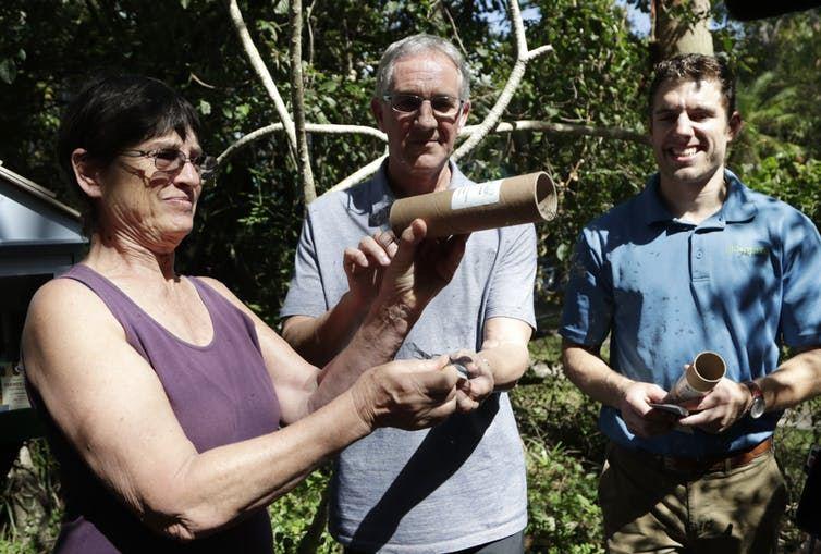 La résidente Annick Sternberg, à gauche, libère les moustiques mâles infectés par Wolbachia, comme le montre Bill Petrie, directeur du centre de contrôle des moustiques du comté de Miami-Dade, à South Miami, Floride, le 8 février 2018. Des milliers de moustiques volent près de Miami pour tester une nouvelle façon de supprimer les populations d'insectes porteurs du virus Zika et d'autres virus. À droite, Patrick Kelly, responsable des opérations sur le terrain pour Mosquito Mate - Crédit : Lynne Sladky/AP Photo