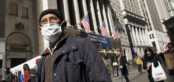 Un homme prenant des précautions au milieu de l'épidémie de coronavirus passe devant la Bourse de New York. (Mark Lennihan / AP)