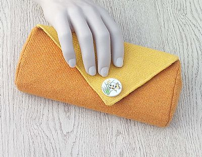 hand with yellow orange clutch bag by roses workshop