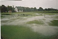 the original clubhouse and a flooded green