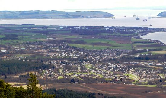 the town of alness with invergordon beyond.  the oil rigs on the cromarty firth are near to the sutors of cromarty.  the cromarty firth then leads into the moray firth.