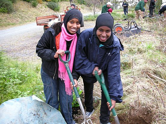 girls from a multi-faith group planting commemorative trees at penrhyn castle