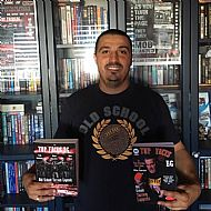 author-gilly-black-holding-both tfbg-ostl-book- bulgarian and english editions- infront of his home library in varna