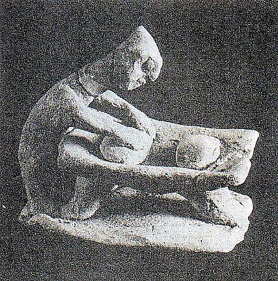 a clay figurine kneading dough in a trough