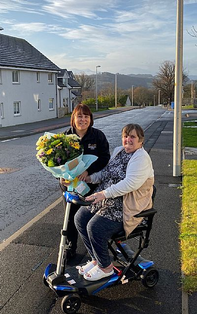 picture of 200th customer receiving a bouquet from carol elliot
