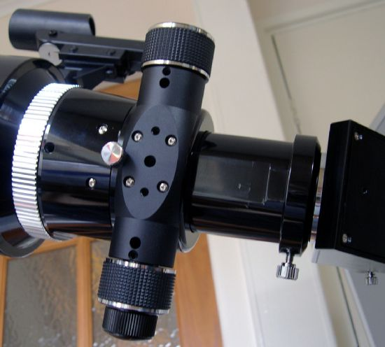 the underside of the focuser, showing the coars and fine focus knobs, hole for the recessed tension adjuster, and the locking collet against the body of the tube assembly.