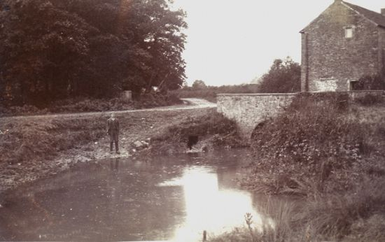 the figure in this photograph is standing at the spot where the car plunged into the mill race.
