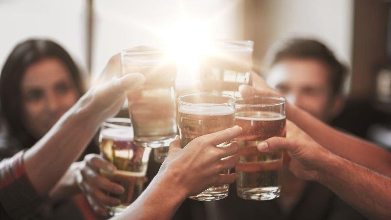 Varias personas hacen un brindis con bebida durante una barra libre