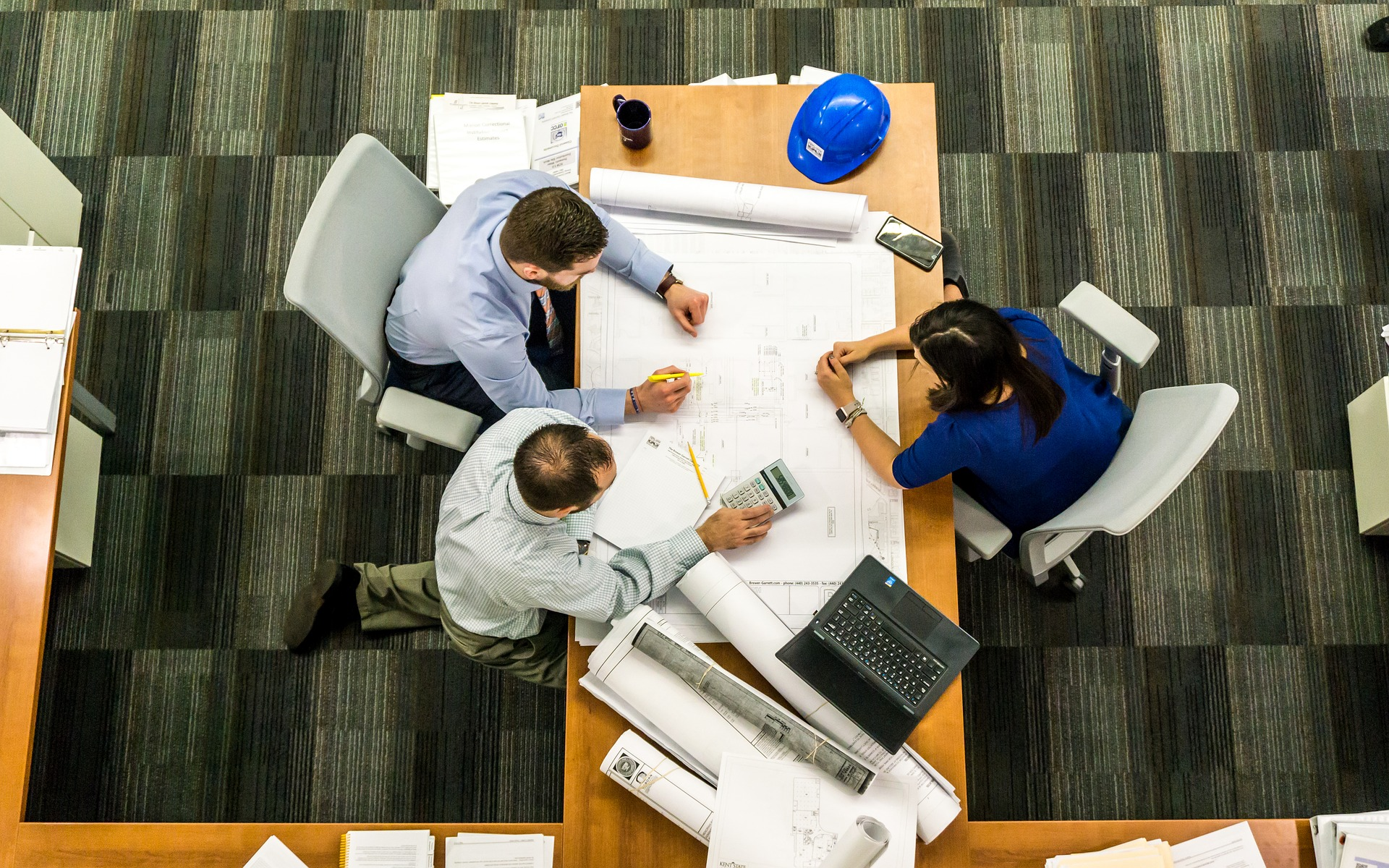 Overhead view of meeting table and three people around with calculators and paper