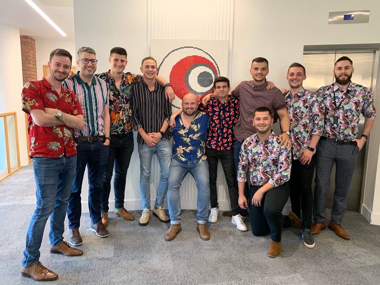sales-i team in fun shirts in front of sales-i logo.