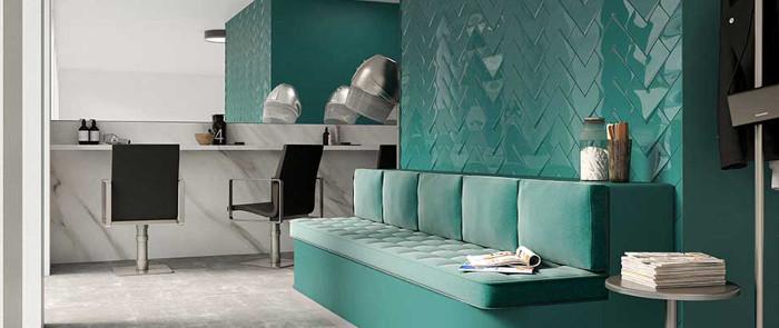 Salon fryzjerski z sofą i płytkami w odcieniach butelkowej zieleni