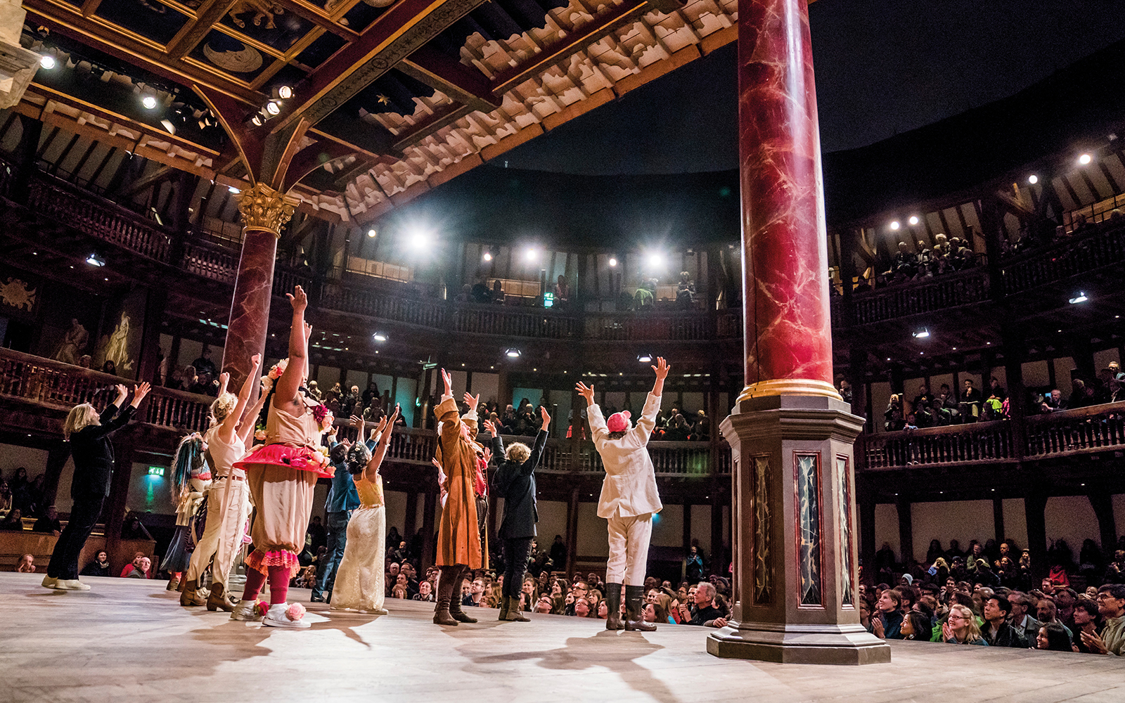 Actors on a stage all stand to bow with their arms in the air