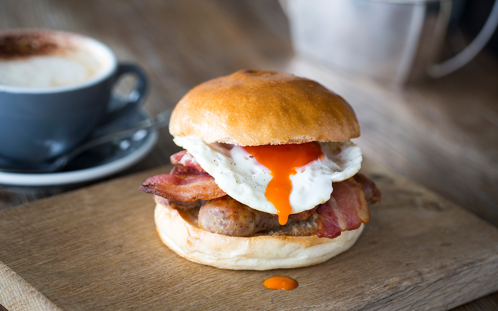 Photo of a breakfast brioche bun with cumberland sausage, smoked streaky bacon and a legbar fried egg.