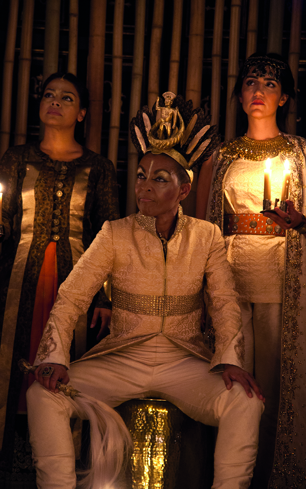 An actor in a white suit sits on a throne wearing a gold crown