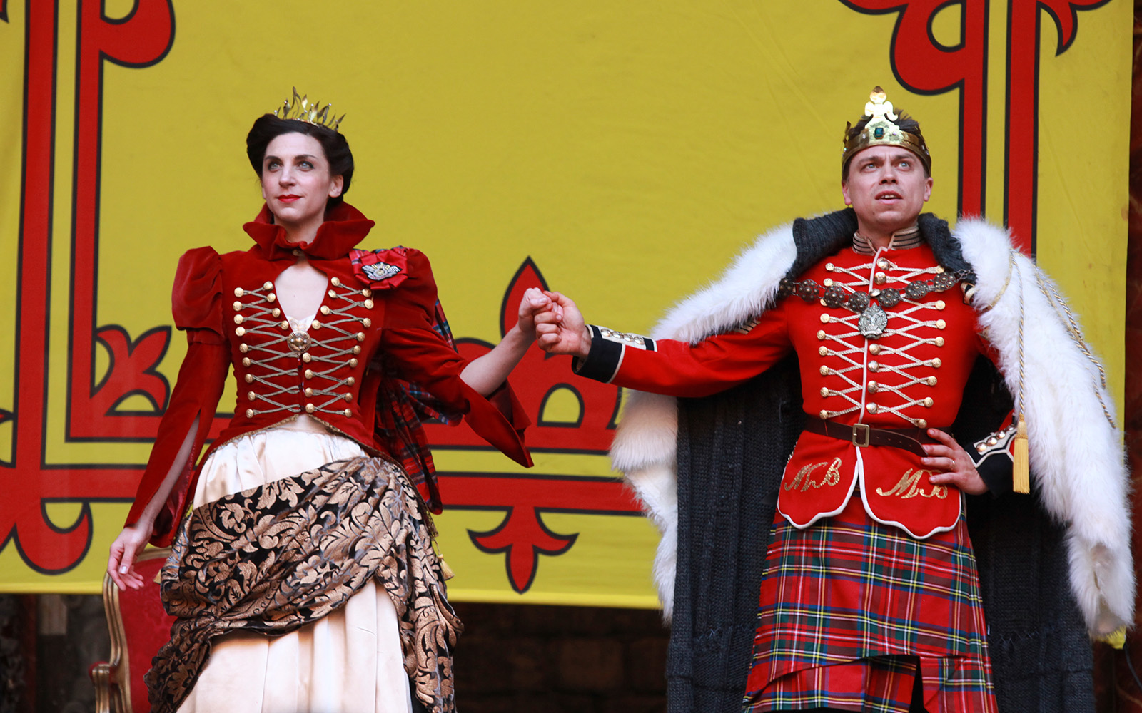 Macbeth and Lady Macbeth dressed in royal garments hold hands