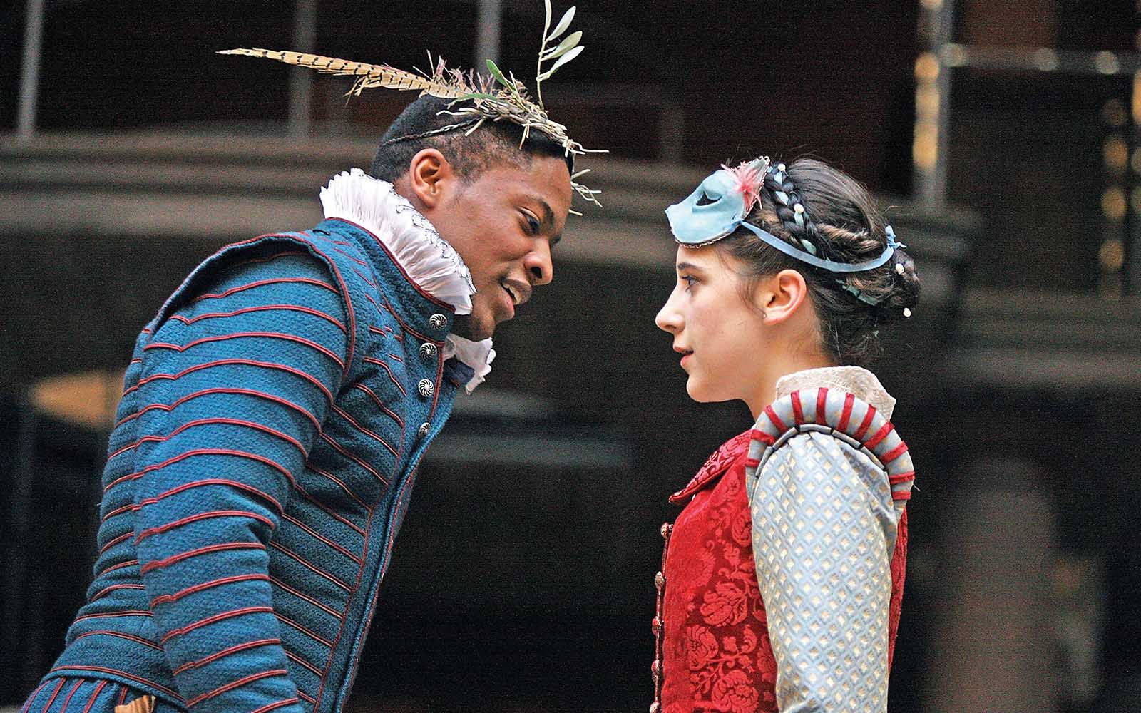 A man and woman stand facing each other on stage