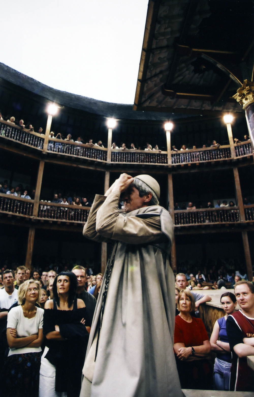 A man holding his hands up to his face stands in the Yard of the Globe Theatre, surrounded by audience members.