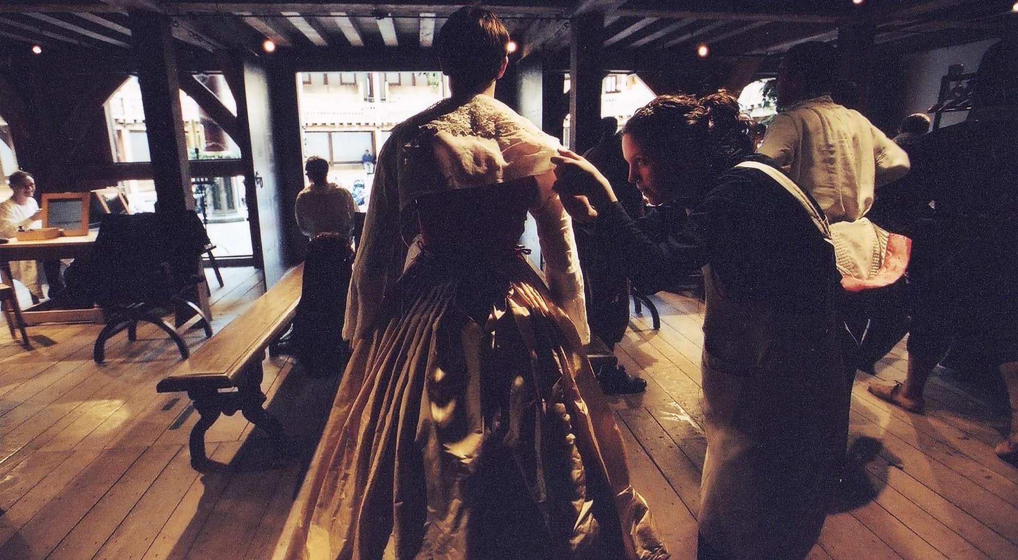 A backstage view of the Globe Theatre, wear a woman helps a man get in to his Elizabethan dress.