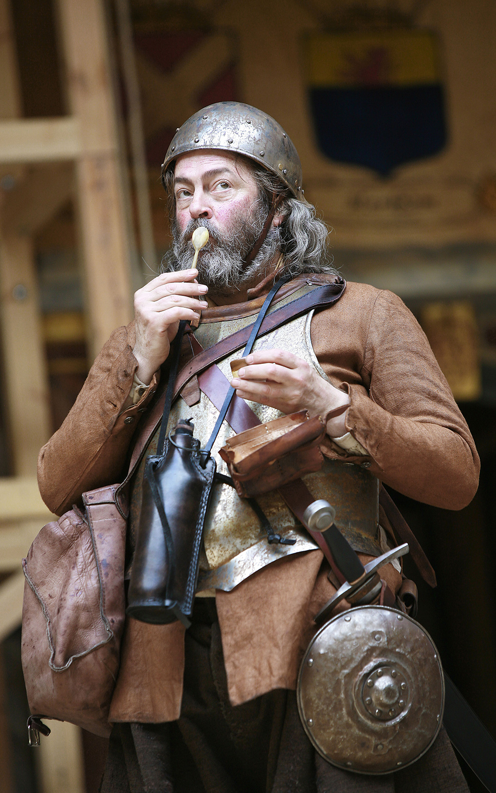 Actor on stage with a wooden spoon on there mouth