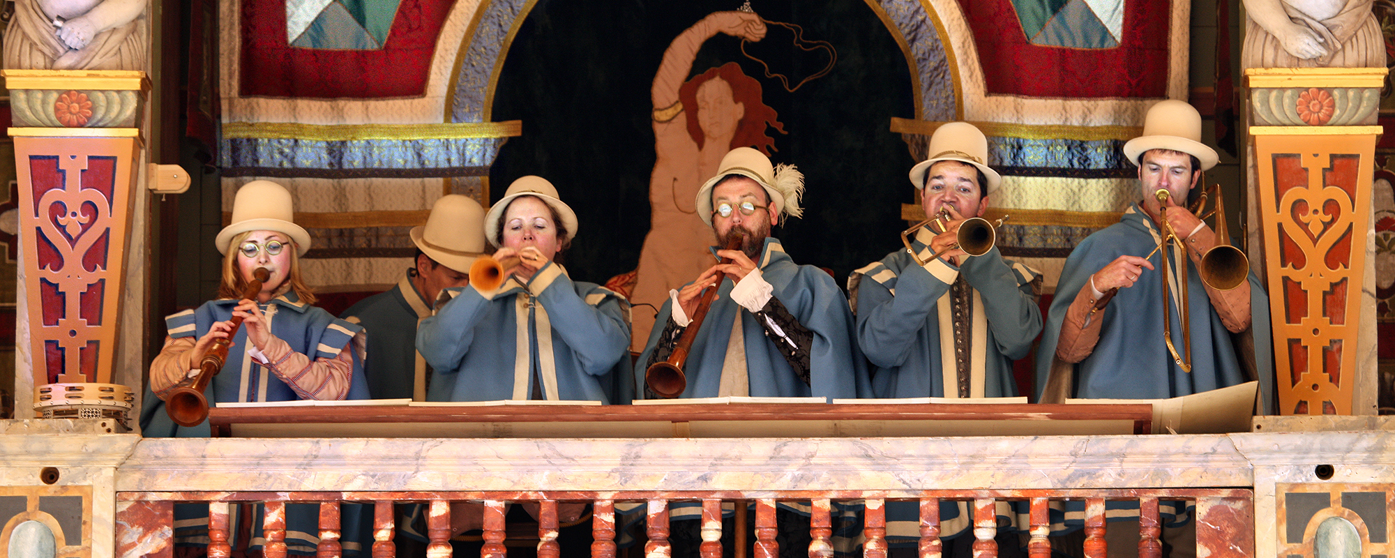 Five musicians stand in the gallery of the Globe Theatre, playing their musical instruments.