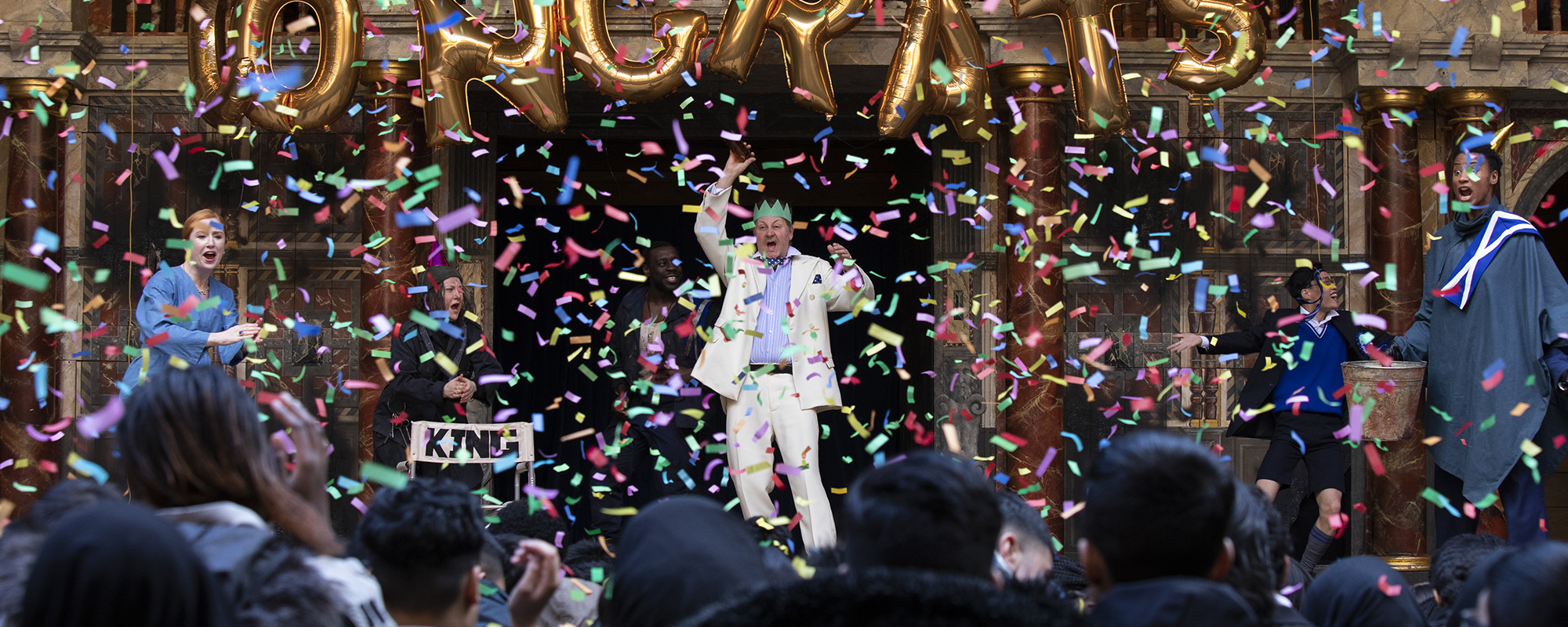 Actors on stage dancing at a party and confetti falling all around them