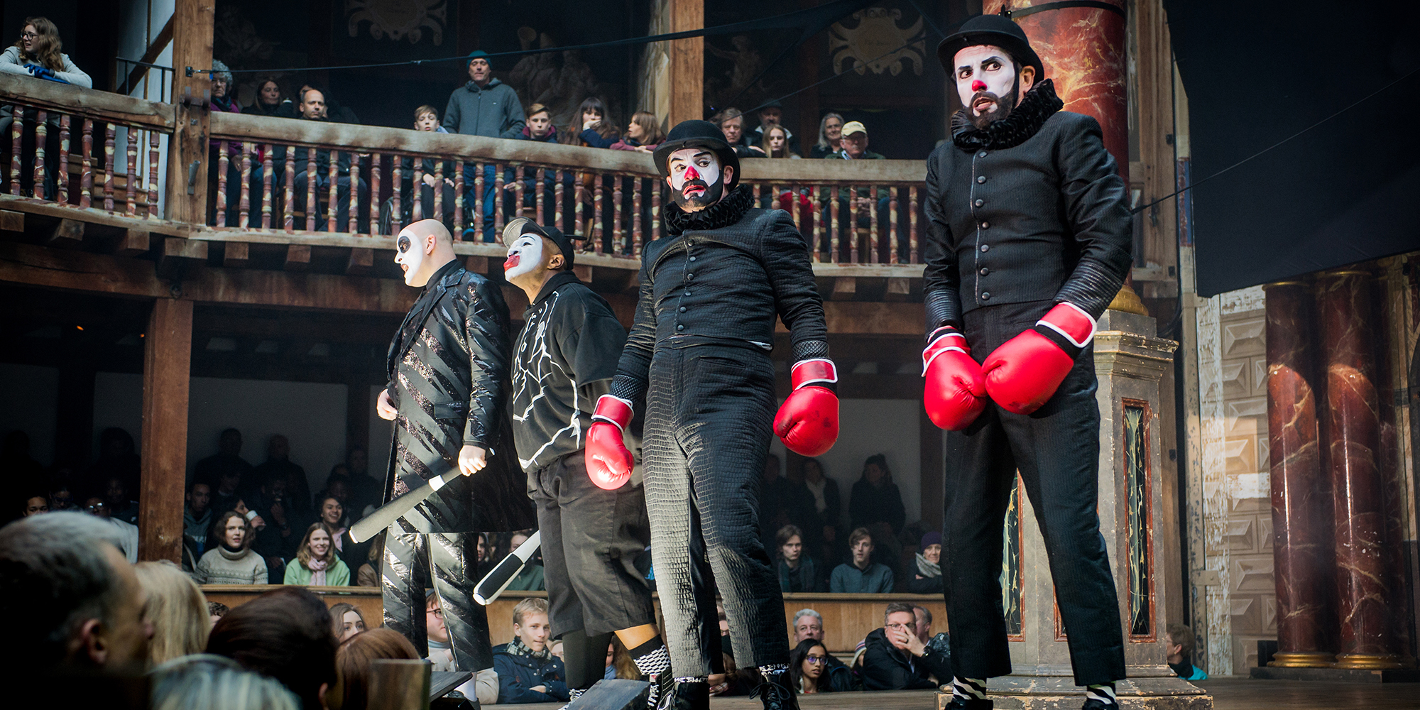Four people wearing black, in clown makeup, and wearing red boxing gloves.