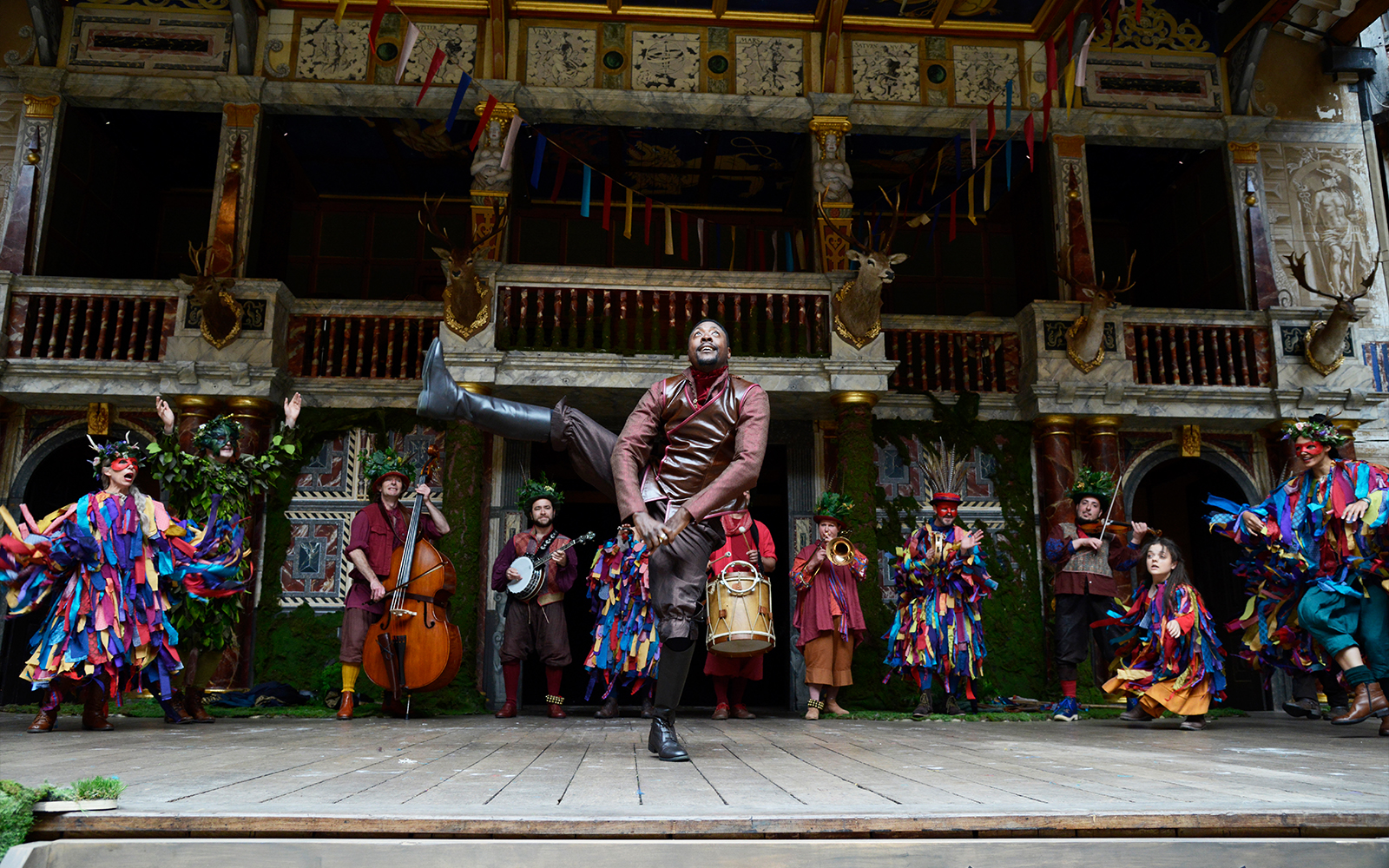 A actor kicks high in the air while others dance around him in colourful costumes